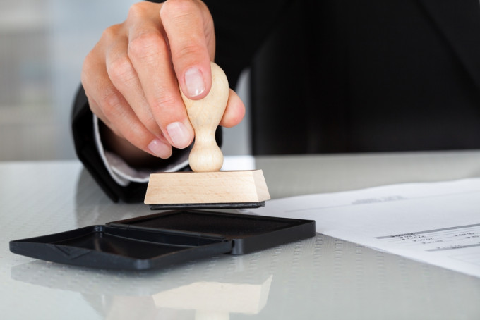 Close-up Of Business Man Hand Pressing Rubber Stamp On Document