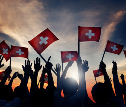 Group of People Waving Switzerland Flags in Back Lit