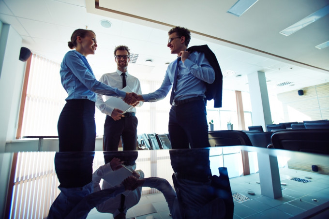 Two partners handshaking after signing agreement in office